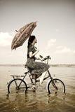 La muchacha va para un paseo del ciclo en el agua con el paraguas Fotografía de archivo libre de regalías