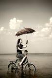 La muchacha va para un paseo del ciclo en el agua con el paraguas Foto de archivo