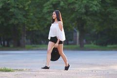 La muchacha va paseo de la penetración del pelo negro del sombrero fotografía de archivo libre de regalías