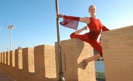 La muchacha vestida en actitud roja se realiza en la acrobacia Foto de archivo