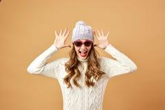 La muchacha vestida en el suéter y el sombrero y las gafas de sol hechos punto blancos se está divirtiendo en un fondo beige en e fotografía de archivo