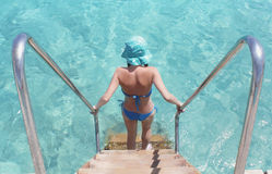 La muchacha viene abajo en agua azul Fotos de archivo libres de regalías
