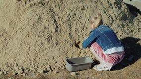 La muchacha vierte la arena en la maceta El cultivar un huerto aficionado almacen de metraje de vídeo