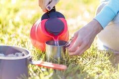 La muchacha vierte el agua de la caldera imagen de archivo libre de regalías
