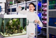 La muchacha vierte el agua en el acuario Imagen de archivo libre de regalías