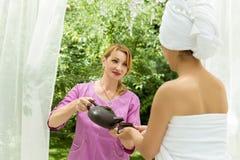 La muchacha vierte té después del balneario Foto de archivo libre de regalías