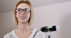 La muchacha vino a la cosmetología, ella es saludada cordialmente por el doctor almacen de video