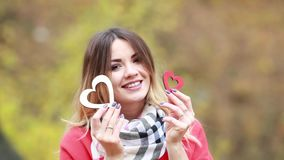 La muchacha y dos corazones de madera en manos en un otoño parquean metrajes