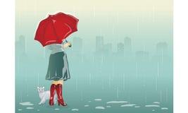 La muchacha y el gato han ocultado de una lluvia debajo de un paraguas Imagen de archivo