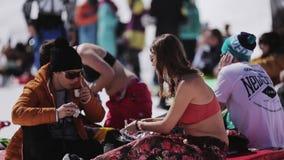 La muchacha y el hombre almuerzan en el colchón inflable Estación de esquí encamp Día asoleado almacen de video