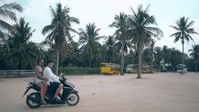 La muchacha y el hombre aparecen en la moto del montar a caballo del cuadrado del asfalto metrajes