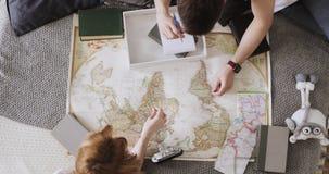 La muchacha y el individuo jovenes de los pares están planeando la ruta que viaja que pone en cama y señalar los lugares para la  almacen de metraje de vídeo