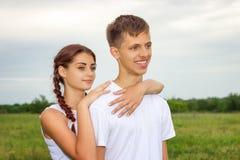 La muchacha y el individuo lindos hermosos jovenes de los pares están colocando el brazo en brazo en un fondo de la naturaleza, e imagenes de archivo