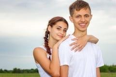 La muchacha y el individuo lindos hermosos jovenes de los pares están colocando el brazo en brazo en un fondo de la naturaleza, e foto de archivo libre de regalías