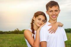 La muchacha y el individuo lindos hermosos jovenes de los pares están colocando el brazo en brazo en un fondo de la naturaleza, e fotos de archivo libres de regalías