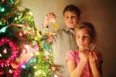 La muchacha y el muchacho adornaron el árbol de navidad por los juguetes de cristal en la tarde. Imágenes de archivo libres de regalías
