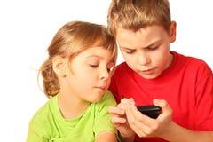 La muchacha y el muchacho buscan interesante en smartphone Fotografía de archivo