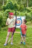 La muchacha y el muchacho con el arco cerca del deporte apuntan Imagen de archivo