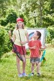 La muchacha y el muchacho con el arco cerca del deporte apuntan Foto de archivo libre de regalías