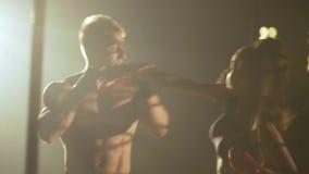 La muchacha y el muchacho están entrenando a la lucha los artes marciales luchan sin reglas en batalla de la jaula sin reglas metrajes