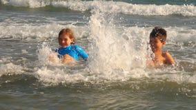 La muchacha y el muchacho felices en una camisa azul golpea el agua con el pie metrajes