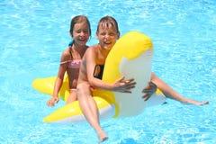 La muchacha y el muchacho felices nadan en el juguete inflable de los niños imagen de archivo