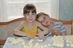 La muchacha y el muchacho hacen las bolas de masa hervida Imagen de archivo