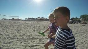 La muchacha y el muchacho hermosos entran descalzo en la arena almacen de video