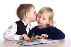 La muchacha y el muchacho leyeron el libro foto de archivo libre de regalías