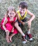 La muchacha y el muchacho tienen un resto en un haystack Foto de archivo