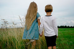 La muchacha y el muchacho van en el campo del verano que lleva a cabo las manos Imagenes de archivo
