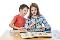 La muchacha y el niño pequeño adolescentes con la lupa que mira el suyo sellan el collec Foto de archivo libre de regalías