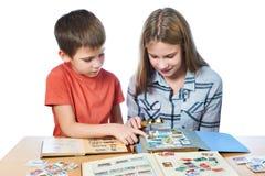 La muchacha y el niño pequeño adolescentes con la lupa que mira el suyo sellan el collec Fotos de archivo libres de regalías
