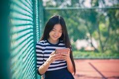La muchacha y el ordenador asiáticos hacen tabletas la situación disponible con el smil dentudo Fotos de archivo