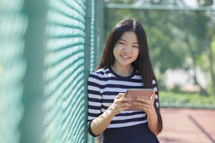 La muchacha y el ordenador asiáticos hacen tabletas la situación disponible con el smil dentudo Foto de archivo