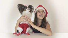 La muchacha y el perro adolescentes hermosos Toy Spaniel Papillon continental en Santa Claus viste alegre la mirada alrededor y Imagenes de archivo