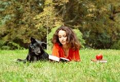 La muchacha y el perro que mienten en una hierba Imágenes de archivo libres de regalías