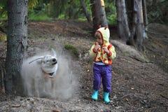 La muchacha y el polvo persiguen la pequeña muchacha divertida y el perro lindo el perro salió de un agujero y sacude apagado el  imagen de archivo