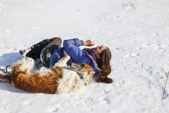 La muchacha y el revolcadero ruso del galgo en la nieve imagenes de archivo