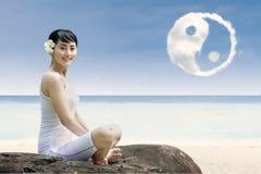 La muchacha y el yin felices yang se nublan en la playa Foto de archivo