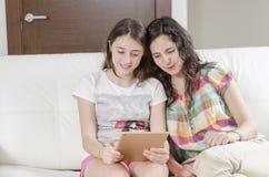 La muchacha y la mujer se está sentando en un sofá que mira su tableta Imágenes de archivo libres de regalías