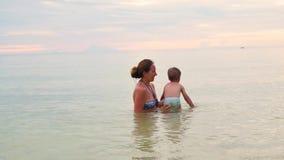 La muchacha y la nadada y el juego del niño en el mar Tiempo de la puesta del sol metrajes