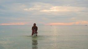La muchacha y la nadada y el juego del niño en el mar Tiempo de la puesta del sol almacen de metraje de vídeo