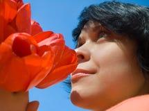 La muchacha y las flores en un fondo del cielo Foto de archivo libre de regalías