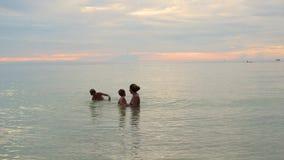 La muchacha y los niños nadan y juegan en el mar Tiempo de la puesta del sol almacen de video