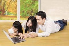 La muchacha y los padres utilizan el ordenador portátil en el piso Imagenes de archivo