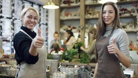 La muchacha y la mujer en los delantales miran en uno a y que la demostración sus pulgares, movimientos de la cámara de la derech almacen de metraje de vídeo