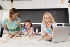 La muchacha y su madre están cocinando una torta hecha en casa La abuela se está colocando al lado de ella y mira la receta en el Imagenes de archivo