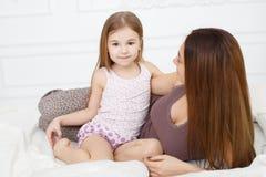 La muchacha y su madre que se sientan en la cama blanca Imagen de archivo libre de regalías