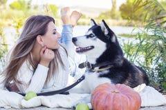 La muchacha y su perro esquimal del perro está mintiendo cerca del río Imagenes de archivo